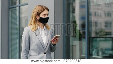 Caucasian Businesswoman In Mask Walking The Street And Texting Message On Mobile Phone. Female Pedes