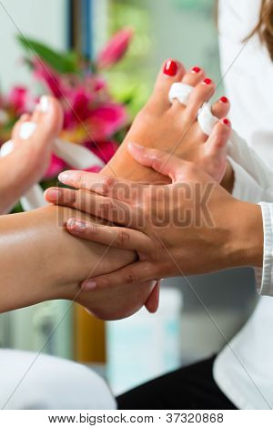 Woman receiving pedicure in a Day Spa, feet nails get polished and she is getting a foot massage