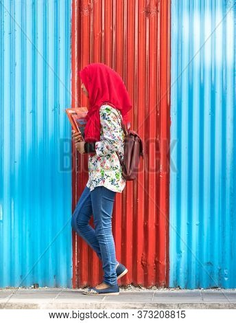 Male, Maldives - February 11th, 2019: A Female Student Wearing Hijab Walking Over A Corrugated Wall