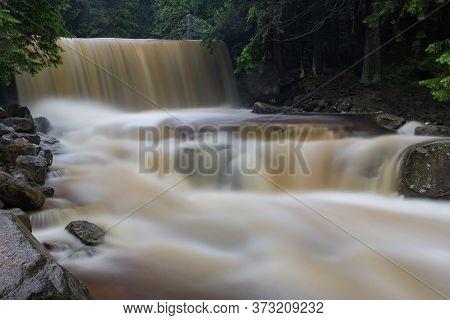 Waterfall In A Mountain Area. Mountain River Flowing Through Rocky Terrain.