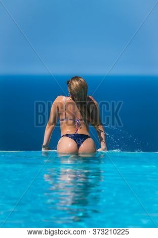 Summer Lifestyle In An Infinity Pool With A Young Blonde Caucasian Woman In A Pink And Purple Bikini