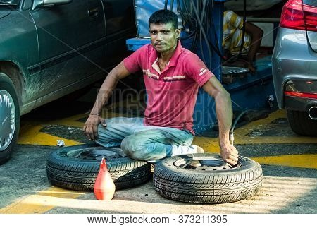 Galle, Sri Lanka - February 18th, 2019: A Sri Lankan Tyre Repairman Inflating A Tyre In Galle, Sri L