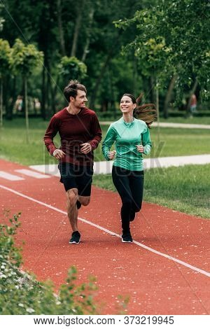 Focus Of Sportswoman Smiling At Boyfriend While Jogging In Park