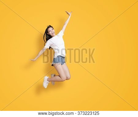 Happy Young Woman Jumping And Looking At The Camera Over Yellow Background