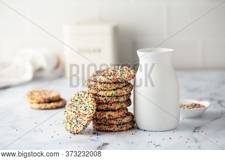 Sugar Cookies With Sprinkles And A Bottle Of Milk On White Background