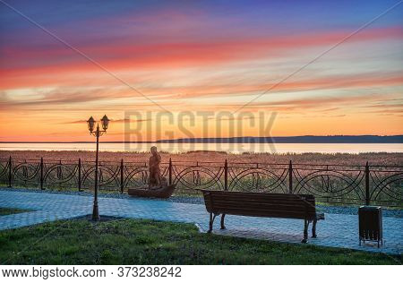 Beautiful Pink Sunset Over Lake Galich In The Kostroma Region, A Wooden Sculpture, A Lantern And A B