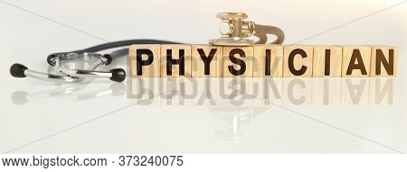 Physician The Word On Wooden Cubes, Cubes Stand On A Reflective White Surface, On Cubes - A Stethosc