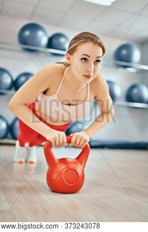 Professional sports and healthy lifestyle. Beautiful girl athlete performs strength exercises with a kettlebell. Weightlifting, bodybuilding.