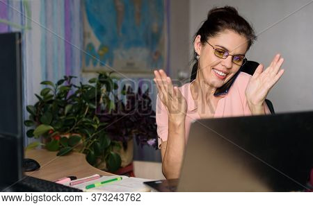 Overjoyed Young Woman In Pink Shirt Working Home Near Laptop, Holds Phone With Her Shoulder, Talks A
