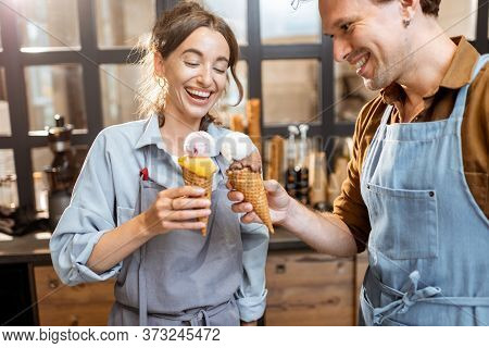 Two Sellers Cheering With Yummy Ice Creams In Waffle Cone, Having Fun While Selling Ice Cream At The
