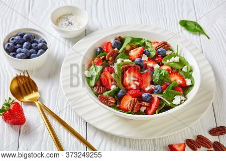 Strawberry Blueberry Spinach Summer Salad With Pecan Nuts And Crumbled Feta Cheese In A White Bowl O