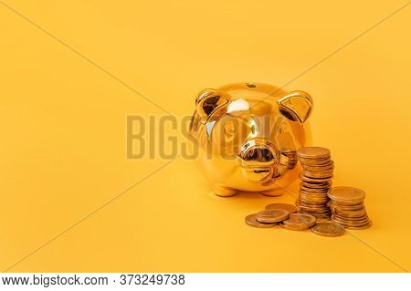 Golden Piggy Bank With Money Towers On Yellow Background. Stack Of Euro Coins Near Golden Money Box.