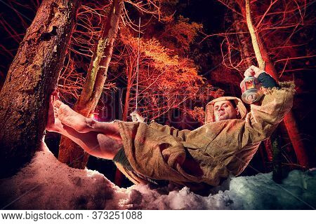 Medieval Monk In Canvas Sackcloth Robe With Lattern Resting On Snow In Dark Forest And Red Light On