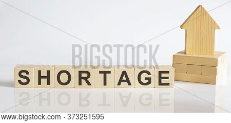 Shortage -wooden Blocks With A Miniature House On White Background