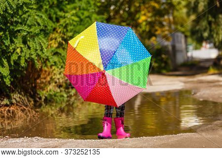Legs Of Child In Rainboots Standing In Puddle