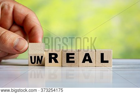 The Hand Turns The Wooden Cube And Changes The Word Unreal To Real