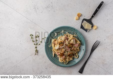 Top View Pasta Fettuccine With Mushrooms, Bacon And Parmesan Cheese In White Plate With Fork On A Li