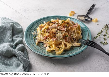 Close Up Pasta Fettuccine With Mushrooms, Bacon, Parmesan Cheese In White Plate With Fork And Napkin