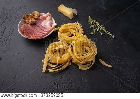 Ingredients Of Pasta Fettuccine With Mushrooms, Bacon And Parmesan Cheese. Raw Food On A Dark Graphi