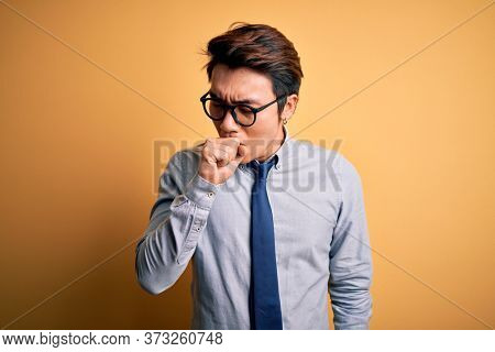 Young handsome chinese businessman wearing glasses and tie over yellow background feeling unwell and coughing as symptom for cold or bronchitis. Health care concept.