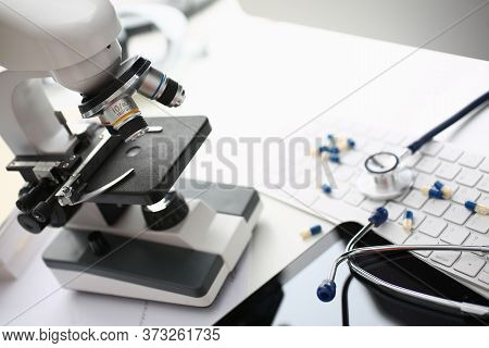 Close Up Of White Table With Laboratory Optical Microscope, Pharmaceutical Drugs, Keyboard And Medic