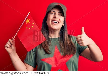 Beautiful patriotic woman wearing t-shirt with red star communist symbol holding china flag smiling happy and positive, thumb up doing excellent and approval sign