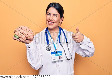 Young beautiful psychiatrist woman wearing stethoscope holding brain over yellow background smiling happy and positive, thumb up doing excellent and approval sign