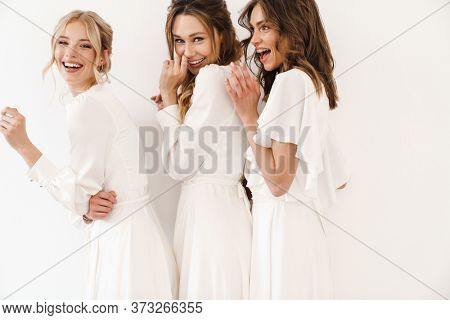 Photo of cheerful charming three women hugging and laughing at camera isolated over white wall