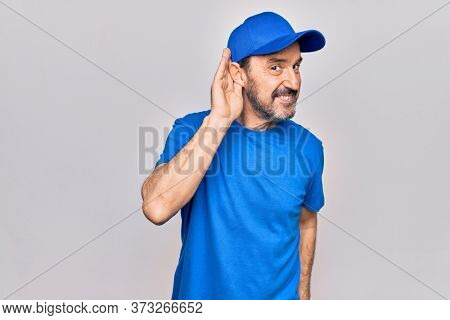 Middle age handsome deliveryman wearing cap standing over isolated white background smiling with hand over ear listening and hearing to rumor or gossip. Deafness concept.