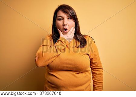 Beautiful brunette plus size woman wearing casual sweater over isolated yellow background Looking fascinated with disbelief, surprise and amazed expression with hands on chin