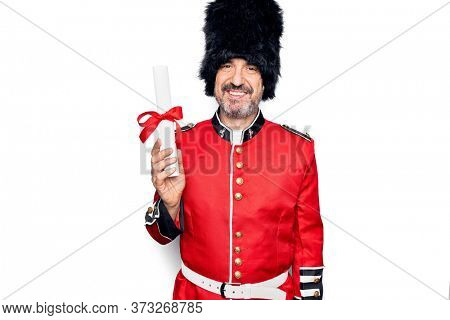 Middle age handsome wales guard man wearing traditional uniform holding diploma degree looking positive and happy standing and smiling with a confident smile showing teeth
