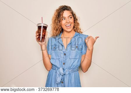 Beautiful blonde woman with blue eyes drinking cola beverage using straw to refreshment pointing and showing with thumb up to the side with happy face smiling