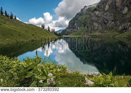 Alpine Landscape Of Mountains With A Mirror Reflection In The Lake. Tourism In Switzerland.