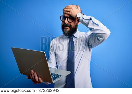 Handsome bald business man with beard working using laptop over blue background stressed with hand on head, shocked with shame and surprise face, angry and frustrated. Fear and upset for mistake.