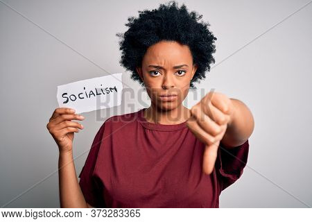Young African American afro politician woman with curly hair socialist party member with angry face, negative sign showing dislike with thumbs down, rejection concept