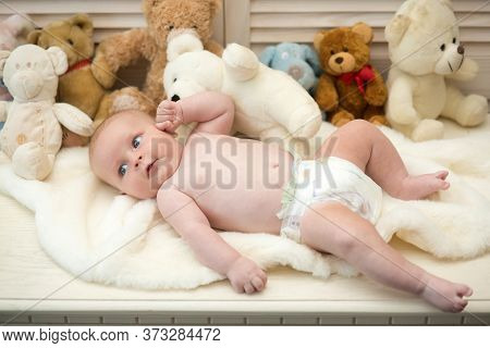 Baby Lying On White Duvet. Infant With Blue Curious Eyes