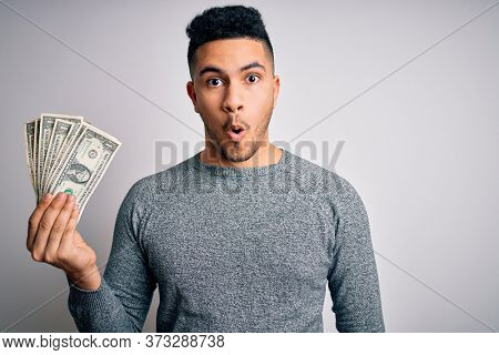 Young handsome man holding bunch of dollars banknotes over isolated white background scared in shock with a surprise face, afraid and excited with fear expression
