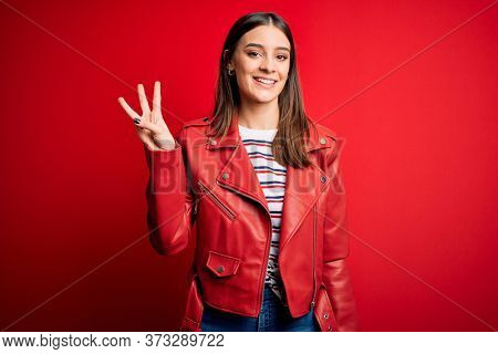 Young beautiful brunette woman wearing casual jacket standing over red background showing and pointing up with fingers number three while smiling confident and happy.