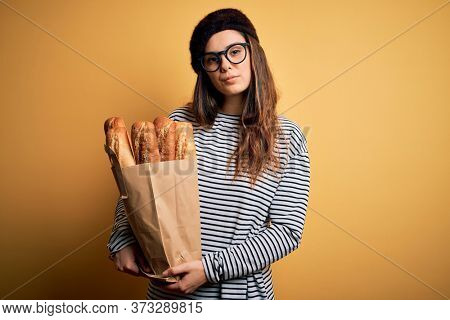 Young beautiful brunette french woman wearing beret holding paper bag with baguettes with a confident expression on smart face thinking serious