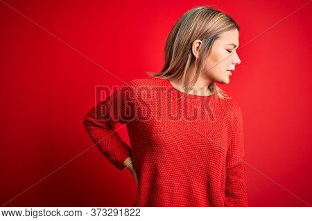 Young beautiful blonde woman wearing casual sweater over red isolated background Suffering of backache, touching back with hand, muscular pain