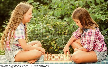 Spend Time Together. Family Time. Two Concentrated Girls Play Chess. Chess Playing Sisters. Skilled