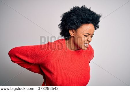 Young beautiful African American afro woman with curly hair wearing red casual sweater Suffering of backache, touching back with hand, muscular pain