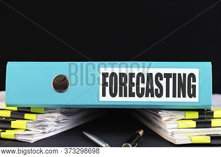 Folder With The Text Forecasting Written On It Lies On A Dark Office Desk With Reports