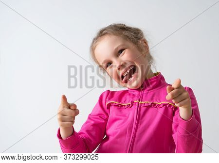 Cute Little Girl In Pink Dress Teasing Someone Bending Her Head To The Side, Lolling And Pointing Wi