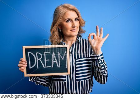 Middle age beautiful blonde dreamer woman holding blackboard with dream message doing ok sign with fingers, excellent symbol