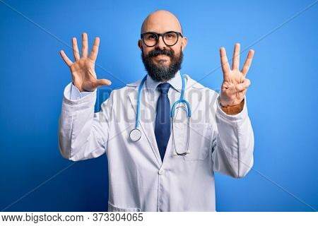 Handsome bald doctor man with beard wearing glasses and stethoscope over blue background showing and pointing up with fingers number eight while smiling confident and happy.