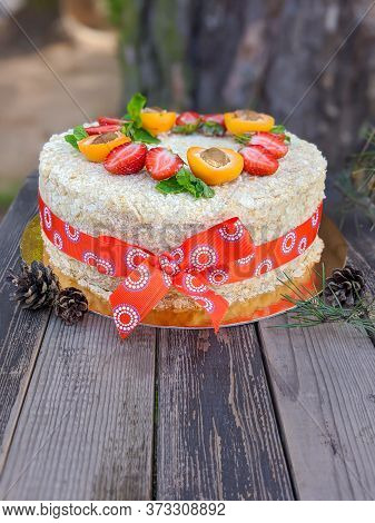 Homemade Layer Cake Napoleon Decorated With Strawberry And Halves Of Apricot On Wooden Rustic Backgr