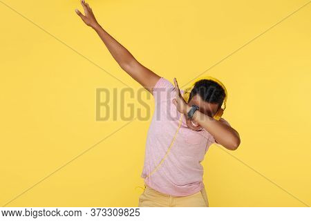 Stylish African American Young Man Dubbing Over Yellow Background.