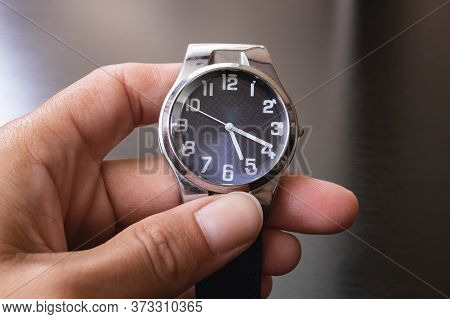 Blue Wristwatch In Hand On Gray Background