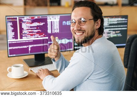 Image of unshaven smiling programmer man showing thumb up while working with computers in office